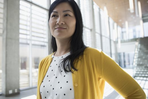 Portrait confident Asian businesswoman in polka dot dress and yellow cardigan looking away